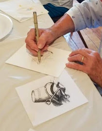 artist drawing with ink on paper