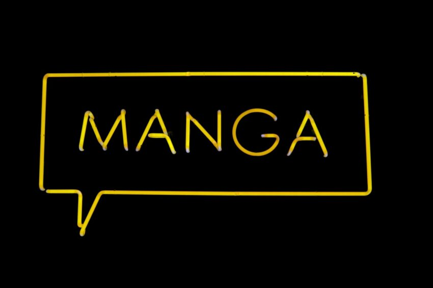"yellow neon sign spelling ""manga"" on black background"