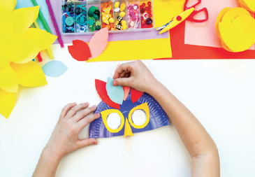 child creating a colorful paper mask