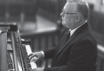 black and white image of andy reid playing the piano