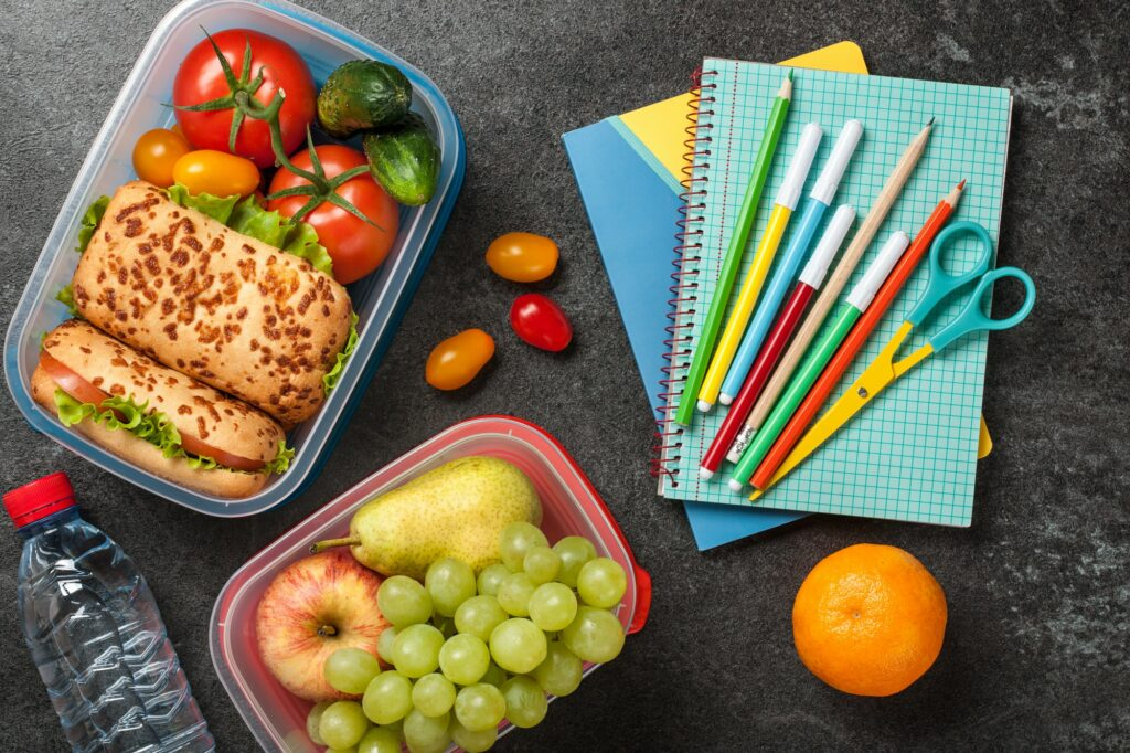 Lunch boxes and school supplies on black