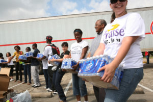 """Houston, TX, September 20, 2008 -- While a crowd, estimate at 3,500, waits for the opening of a volunteer distribution site neighbors join in a """"bucket brigade"""" to unload supplies.. The Federal Emergency Managment Agency (FEMA) works with many volunteer agencies to provide emergency supplies after major disasters. Leif Skoogfors/FEMA"""
