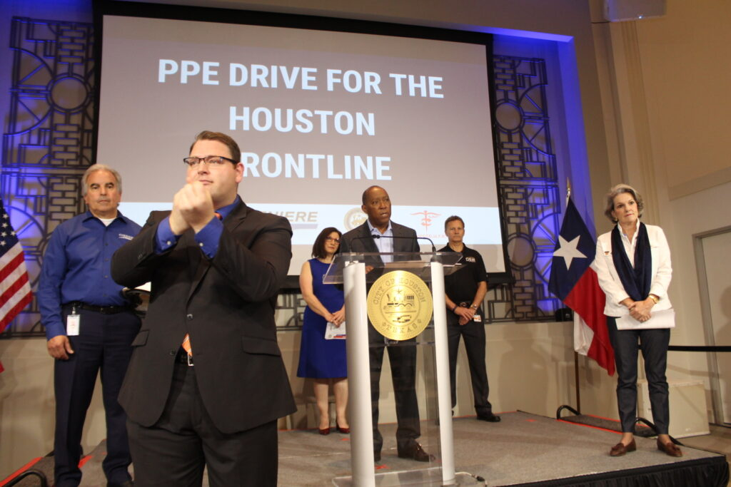 """Mayor Sylvester Turner speaks at the podium in the City Hall Legacy Room during a news conference where he announced the """"PPE drive for the Houston Frontline"""" (which is written on a screen behind him). Representatives from Project CURE, Cheniere Energy, and the Astros Foundation stand socially distant from him on stage. An American Sign Language Interpreter stands in the foreground."""