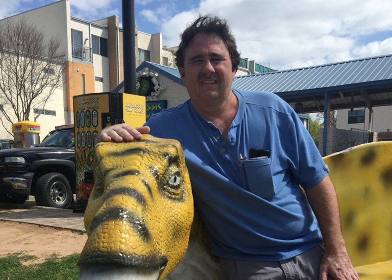 Jurassic Car Wash owner, John Borek, on one of the dinos in front of his business. Photo by: John Kelso, Austin American-Statesman.
