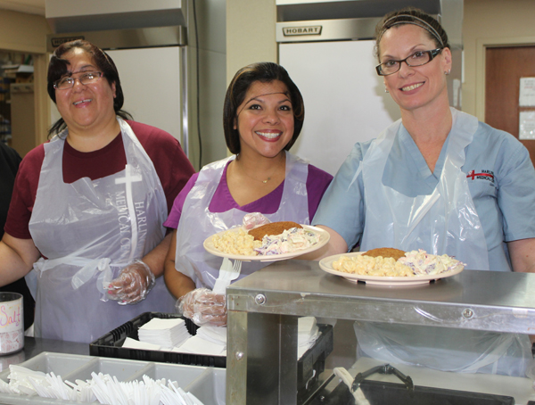 Helping to serve meals to the needy at Loaves & Fishes are Harlingen Medical Center employees Gracie Zarate of the hospital's laboratory; Lisa Aguilar, employee health nurse for Harlingen Medical Center, and Melanie Little of the hospital's Day Patient department.