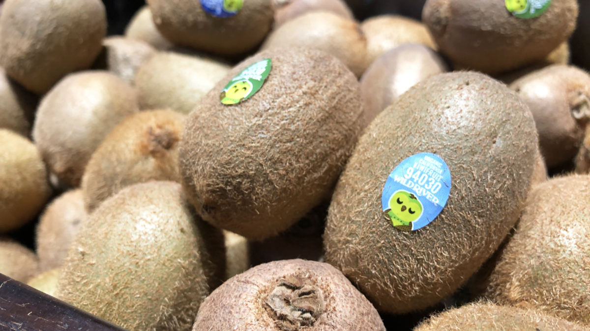 Our Owl Friends and associated kiwi owl logos are trademarks of Wild River Marketing Inc. Designed by Ben Young Landis and Guy Rogers. The photo shows a series of P L U stickers on green kiwifruit stocked at Market 5 One 5 in Sacramento. The stickers read: Organic California Kiwifruit 94030 Wild River, and feature a green kiwi owl.