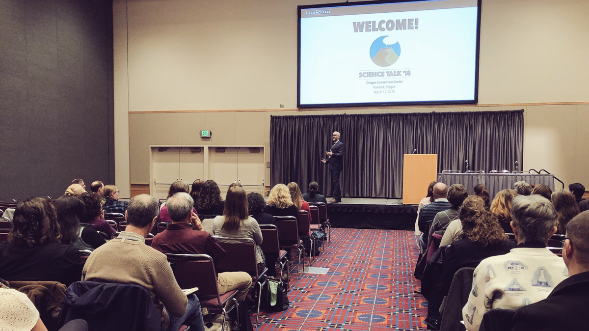 Steven Sobieszczyk opens the events at Science Talk 2018 conference in Portland, Oregon. He is wearing a suit and standing on stage, gesuring to the crowd.