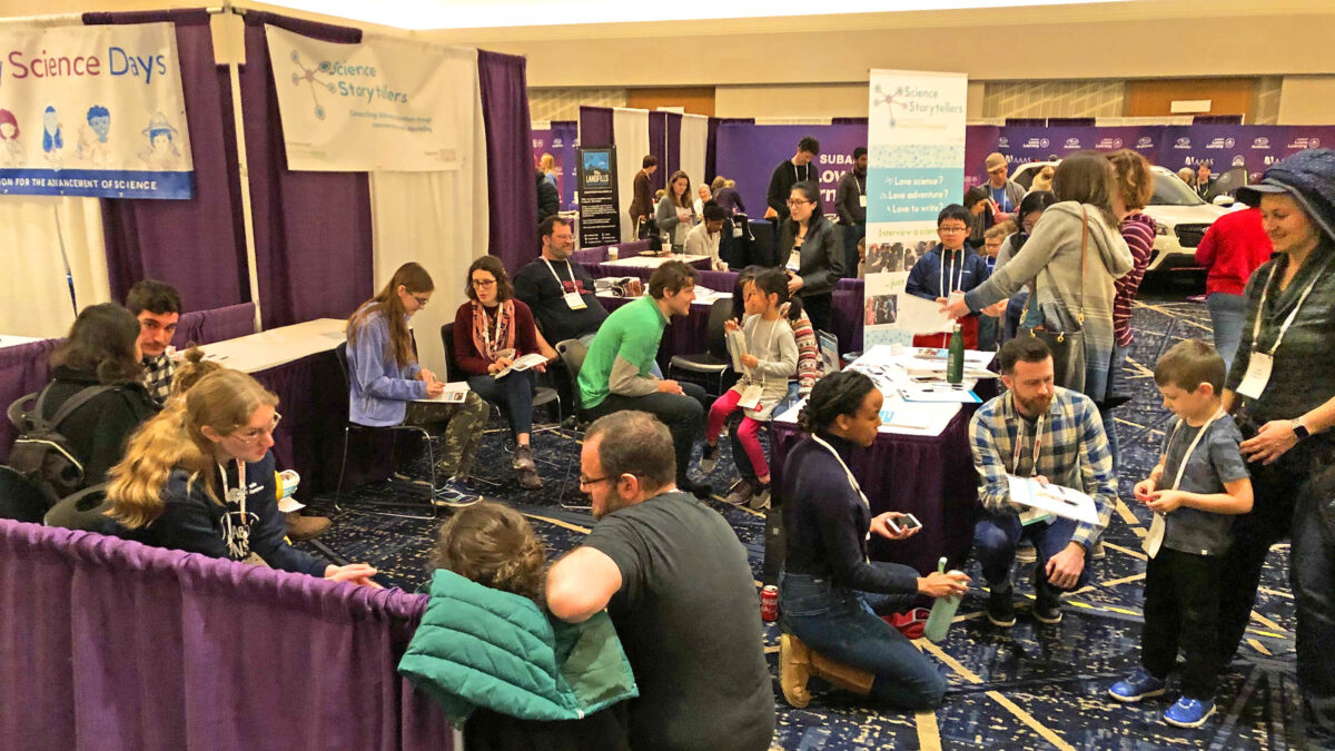 Children and parents gather at the Science Storytellers booth at the Family Science Days public fair hosted in Seattle by the American Association for the Advancement of Science, February 16, 2020. The photo shows scientists of diverse ethnicities and genders seated and being interviewed one-on-one by kids with pen and paper in hand. (Photo by Ben Young Landis for Science Storytellers)
