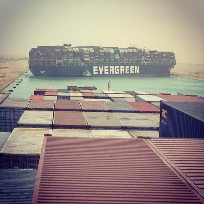 An enormous freight ship, with shipping containers stacked more than 10 layers high like toy blocks, can be seen touching both sides of the Suez Canal. It's so big that a big tractor-digger on the shore looks like a tiny insect. The foreground is stacked containers from the ship from which this photo was taken.