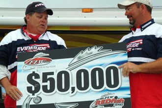 Ray Chagnard (left) and Edward Adams proudly display their first-place check after winning the FLW Redfish Series event at Cocodrie, La. (Photo by Gary Mortenson)