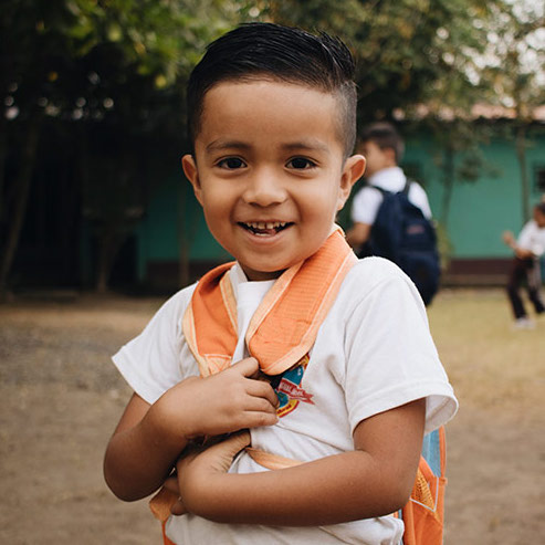 boy with orange backpack on