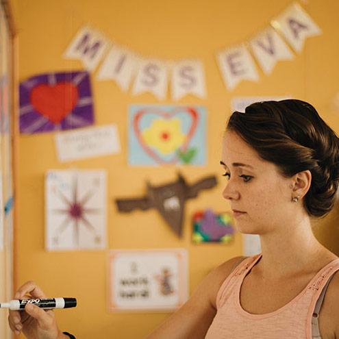 teacher in classroom writing on board
