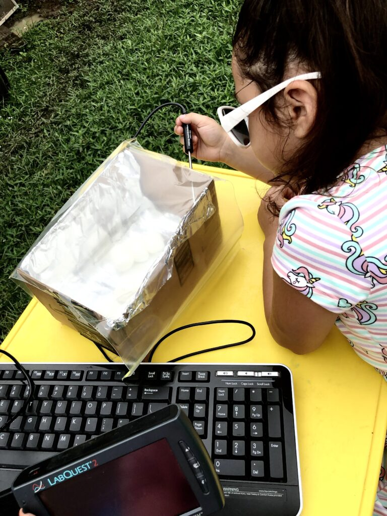 Student using Talking LabQuest to roast marshmallows in a homemade solar oven