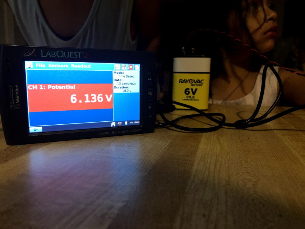 A young girl works with the Talking LabQuest, a differential voltage probe, and a 6V battery