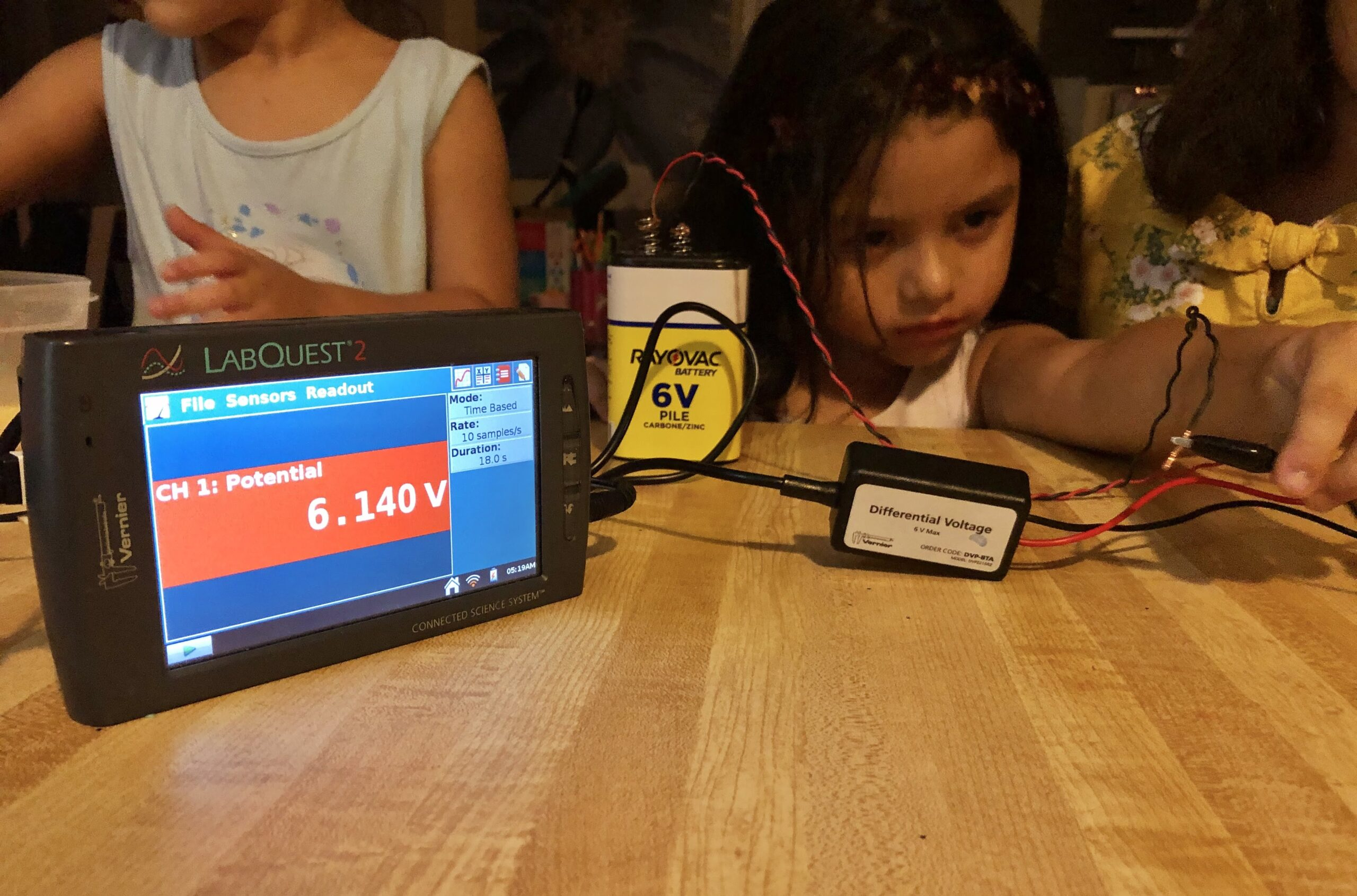 Two young girls clip a lead to a piece of copper and a 6V battery while using the differential voltage probe with the Talking LabQuest