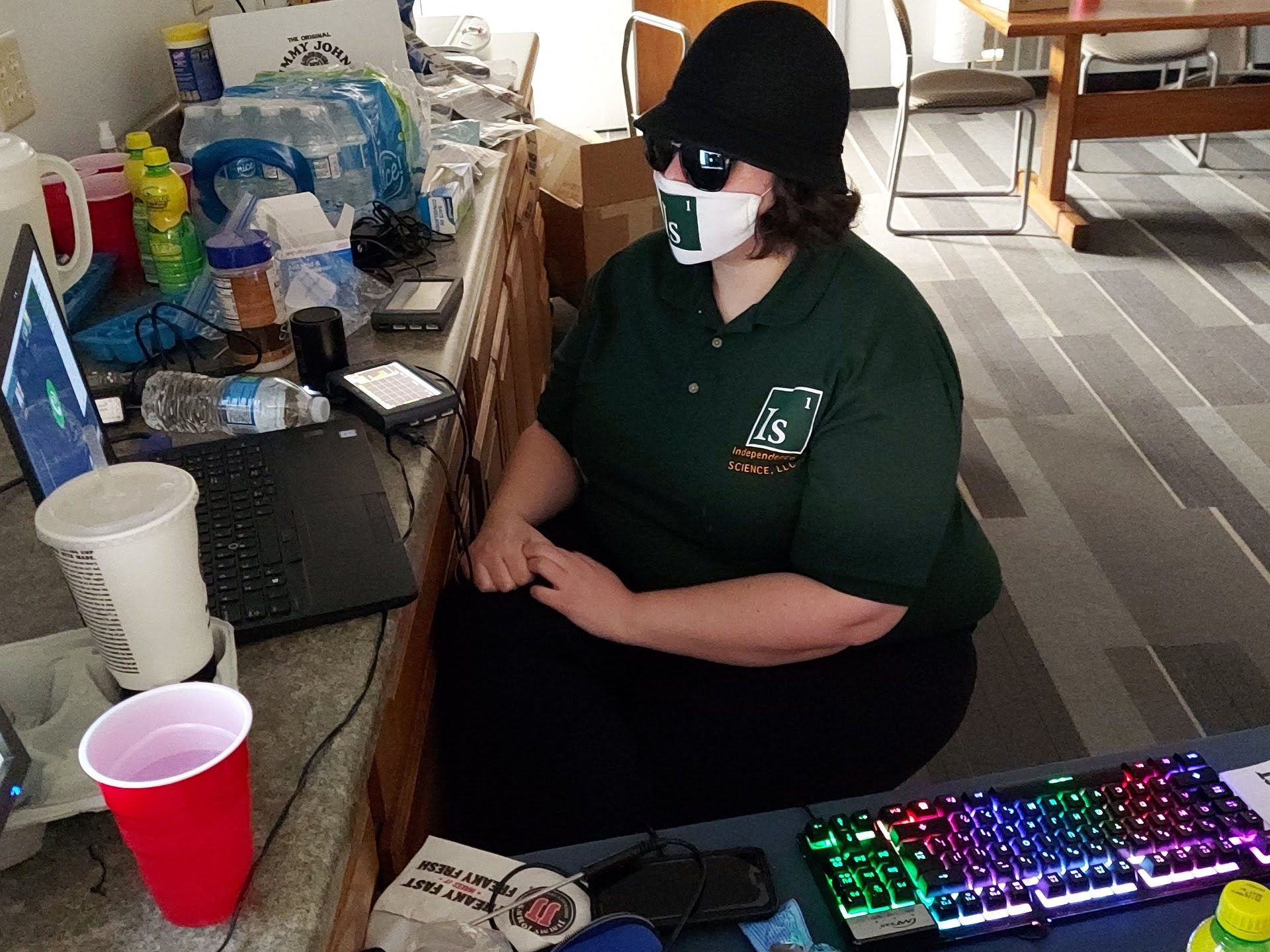 Ashley wears a matching Independence Science polo and face mask while talking to a virtual class