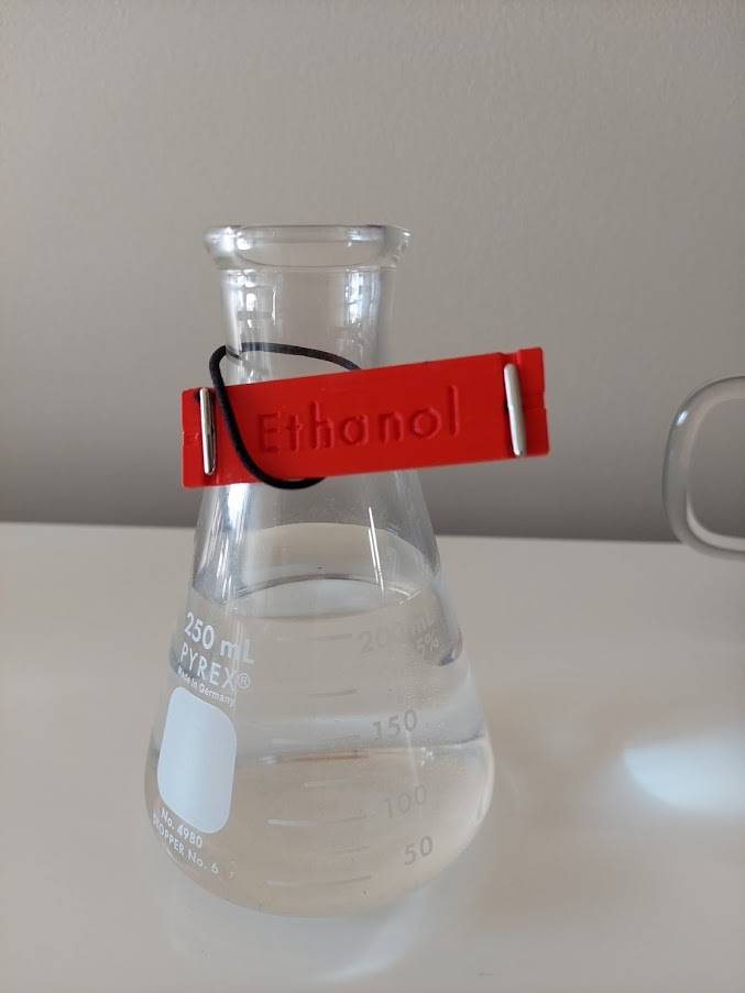 """conical flask with attached Braille Mark label """"Ethanol"""" in engraved text"""