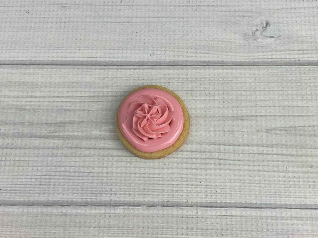 Use star tip with thick royal to add flower for Mother's Day Flower Cookies