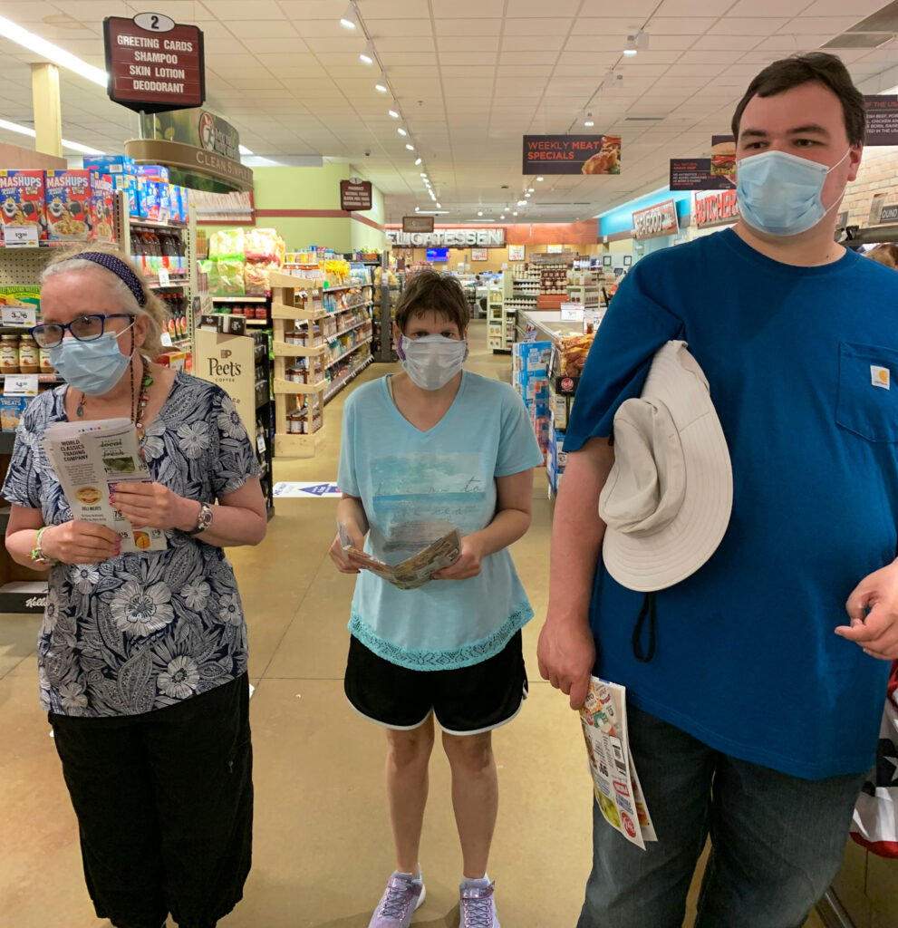 A group stands in a grocery store with flyers in their hands