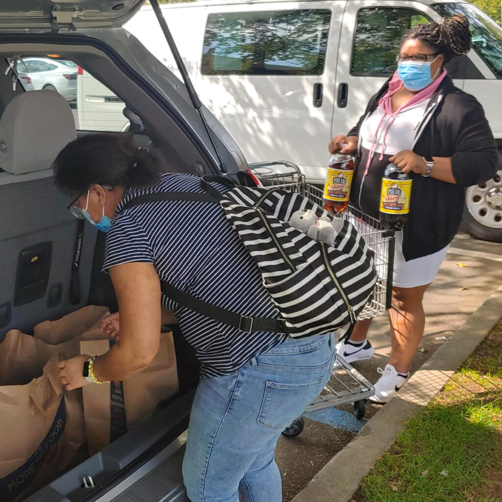 Two women unload groceries into the trunk of a car
