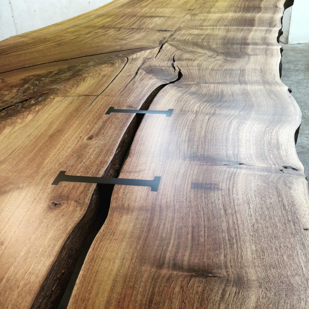 Custom live edge wood slab dining table with a joiners for an elemental crack.
