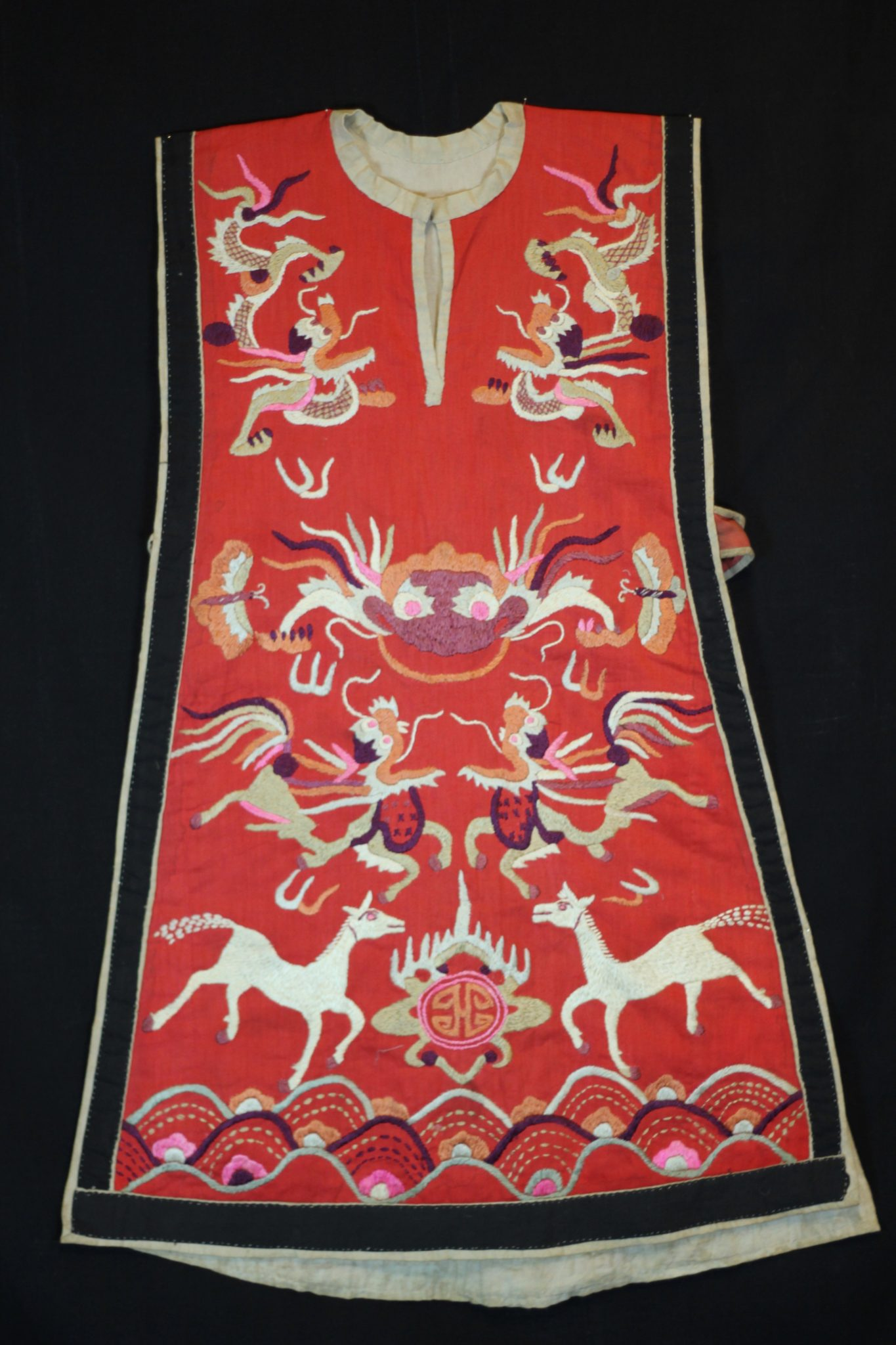 "Dragon Tunic Ritual Costume, Vietnam, Tight Trouser Yao people, Mid 20th c, Cotton, silk embroidery. Worn only by high level shaman. The motif typically includes all the deities of heaven to clothe the shaman in the protection of the universe. Not a vain adornment, it is a reminder of man's place in the hierarchical order. Originally a female costume. Long ago shamans were women and men the providers. Not being encumbered by childbirth and rearing, men replaces women as shamans but retained this part of the sacred costume. 34"" x 24"", $2800"