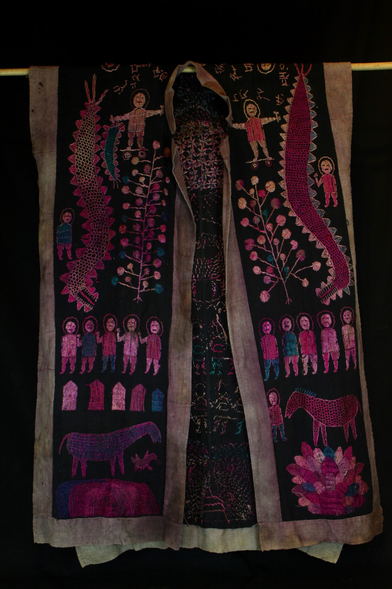 "Dragon Robe/Ritual Cloak, Vietnam, (front view) Yao people, Mid 20th c, Cotton, indigo, silk embroidery. Worn only by high level priest/shaman. The motif typically includes all the deities of heaven to clothe the shaman in the universe for protection. Not a vain adornment, it is a reminder of man's place in the hierarchical order. Originally a female costume. Long ago shamans were women and men the providers. Not being encumbered by childbirth and rearing, men replaces women as shamans but retained this part of the sacred costume. 49"" x 29"", $2200."