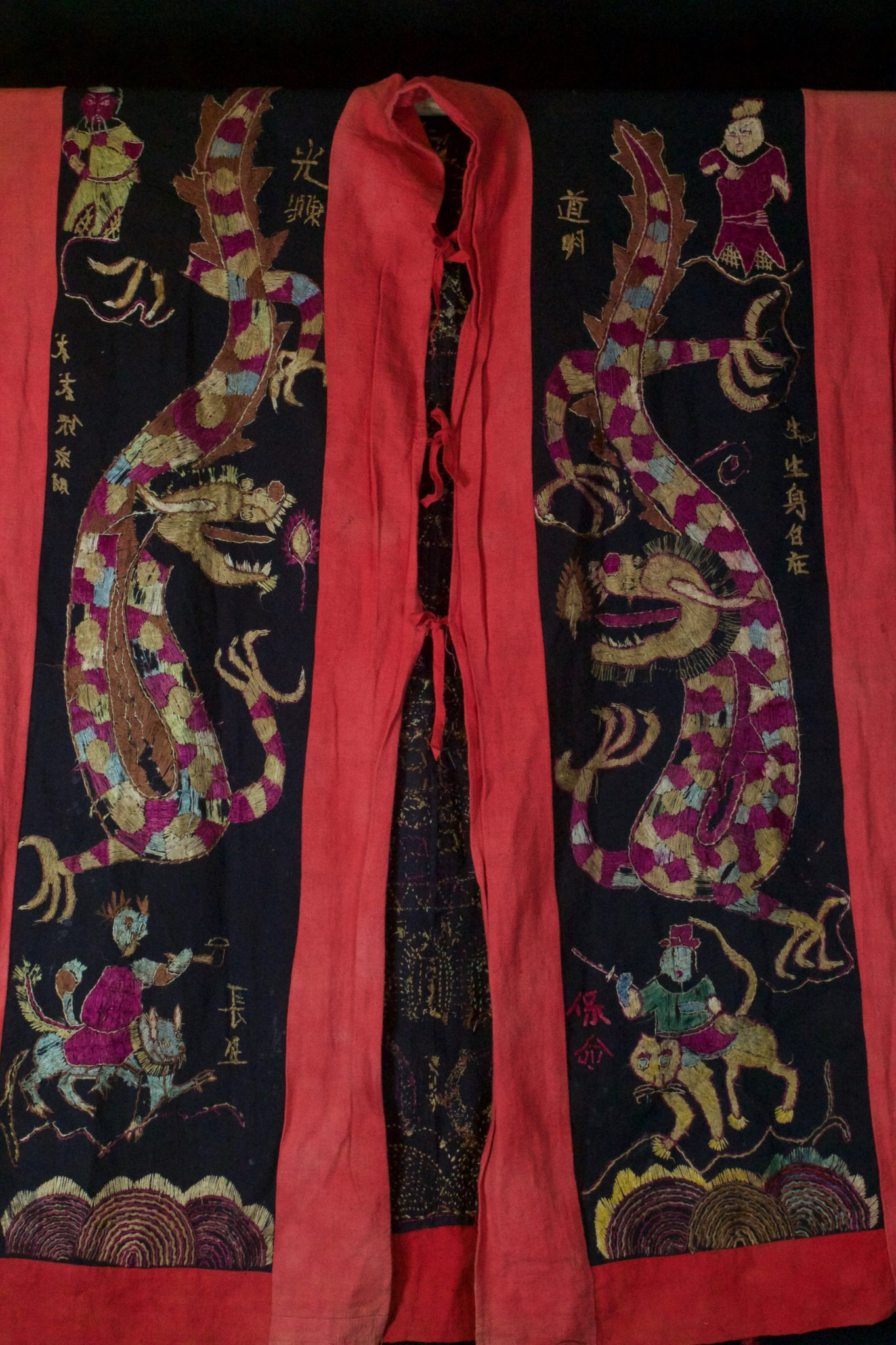 "Dragon Robe/Ritual Cloak (front), Vietnam, Tao people, Early to mid 20th c, Cotton, silk embroidery. Worn only by high level priest/shaman for all ceremonies. The motif typically includes all the deities of heaven to clothe the shaman in the universe for protection. Not a vain adornment, it is a reminder of man's place in the hierarchical order. Originally a female costume. Long ago shamans were women and men the providers. Not being encumbered by childbirth and rearing, men replaces women as shamans but retained this part of the sacred costume. 48"" x 39"", $2700."