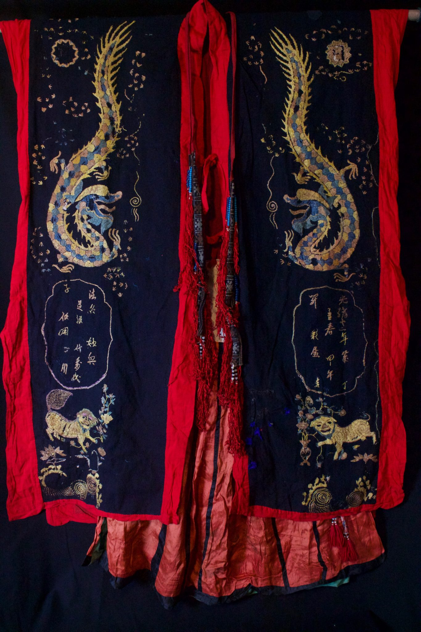 """Dragon Robe (front), Shaman Priest's Costume, complete outfit; Robe, Skirt, Belt, ( Scarf see next image), Vietnam, Tao people, Mid 20th c, Cotton, silk embroidery. Worn by shaman/priests for all ceremonies. The motif typically includes all the deities of heaven to clothe the shaman in the universe for protection. Not a vain adornment, it is a reminder of man's place in the hierarchical order. Long ago shamans were women and men the providers. Not being encumbered by childbirth and child rearing, men replaced women as shaman but retained the same sacred costume. This type of headpiece/scarf is worn by postulant or newly ordained shaman. High level priests will wear a hat made of human hair. Dimensions (49"""" x 42"""" robe); (35"""" x 26"""" skirt); (106"""" x 3"""" belt); (118"""" x 9 ½"""" scarf), $3900 full costume"""