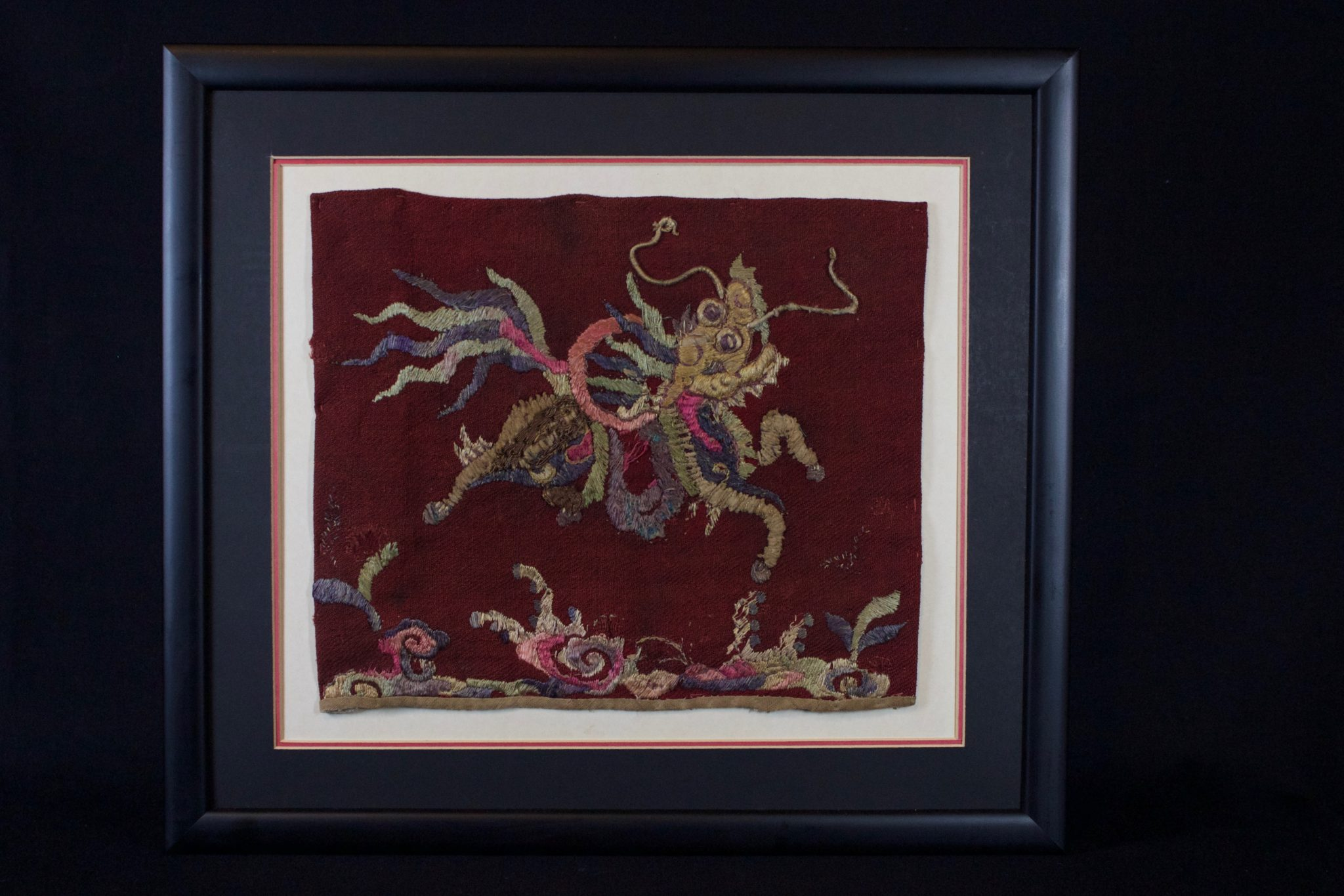 "Sacred Unicorn (Kỳ lân) Panel (rare), Vietnam, Bac Ninh province, Mid 19th c, Red cotton textile with hand embroidered silk and precious-metal-wrapped thread. One of the four sacred animals, the unicorn symbolizes purity, happiness and wealth. If the unicorn appears, many good things will happen. It is often hung over the altar table in pagodas, temples or in homes of traditional families. Its strength and faithful nature are desirable for guarding temples and places of worship. Almost all of these pieces from this time period are portrayed in blue, cream and metallic color schemes. Because of its coloring, this panel is unusual and particularly desirable. 15 ½"" x 17 ½"" x ¾"", $590."