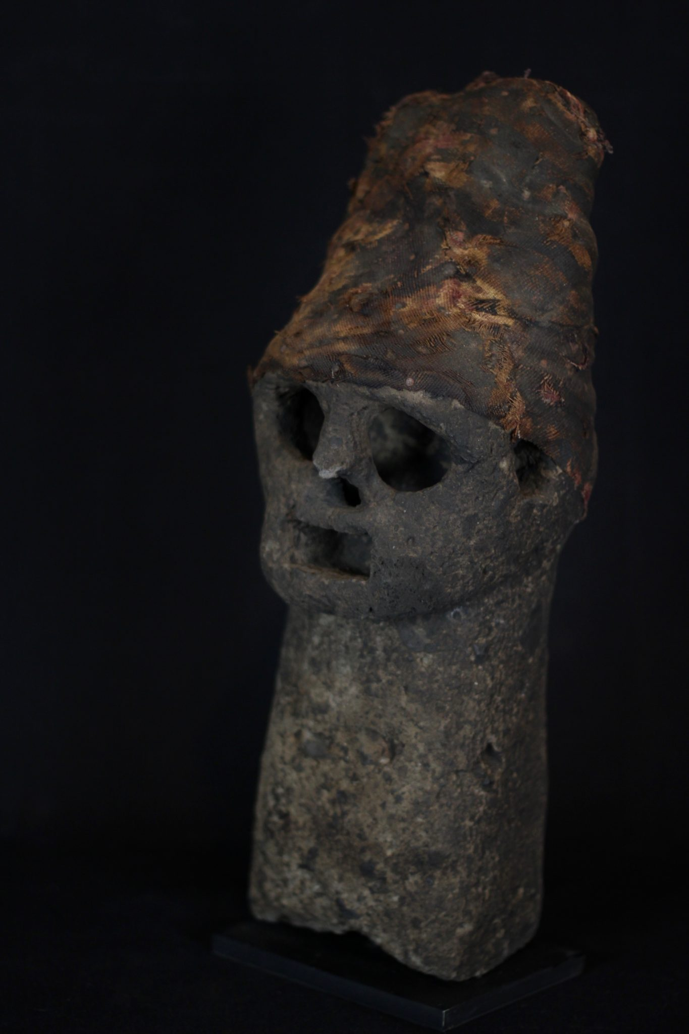 "Volcano God Effigy (exceptionally rare), Flores Island, Lesser Sunda Islands, Indonesia, Manga Lewa Village, Mid 18th c, Stone, cloth. Used by shaman for predicting volcanic eruptions. Passed down through four generations. 15"" x 5 ½ x 5 ¾"", sold"
