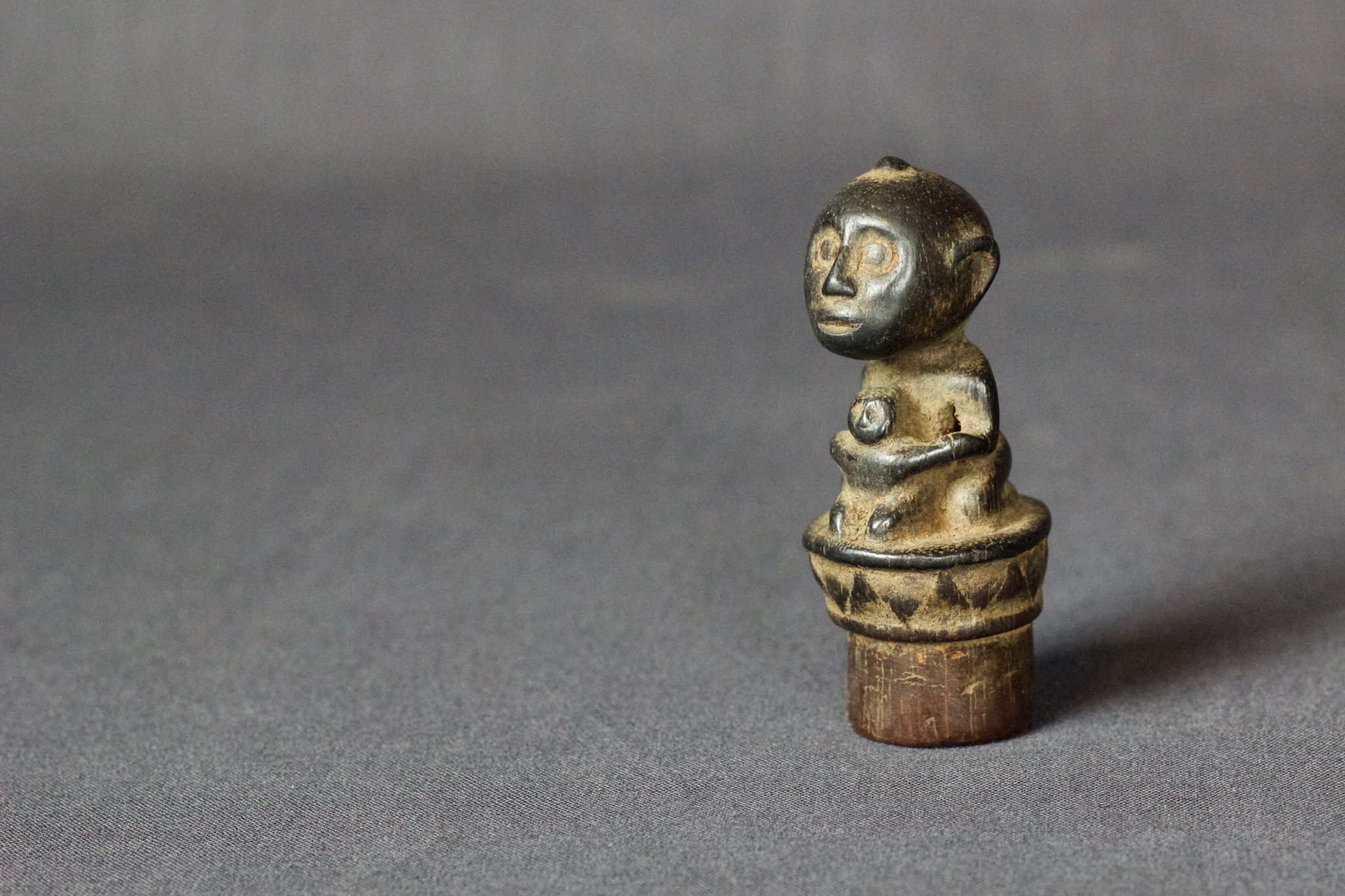 "Shaman Magic Medicine Bottle Stopper, East Sumba Island, Lesser Sunda Islands, Indonesia Mid 19th c, Wood, patinated with use and age. Talisman figure with child, used empower the healing medicine in the bottle. 3"" x 1 ¼"" x 1 ¼"", $80."