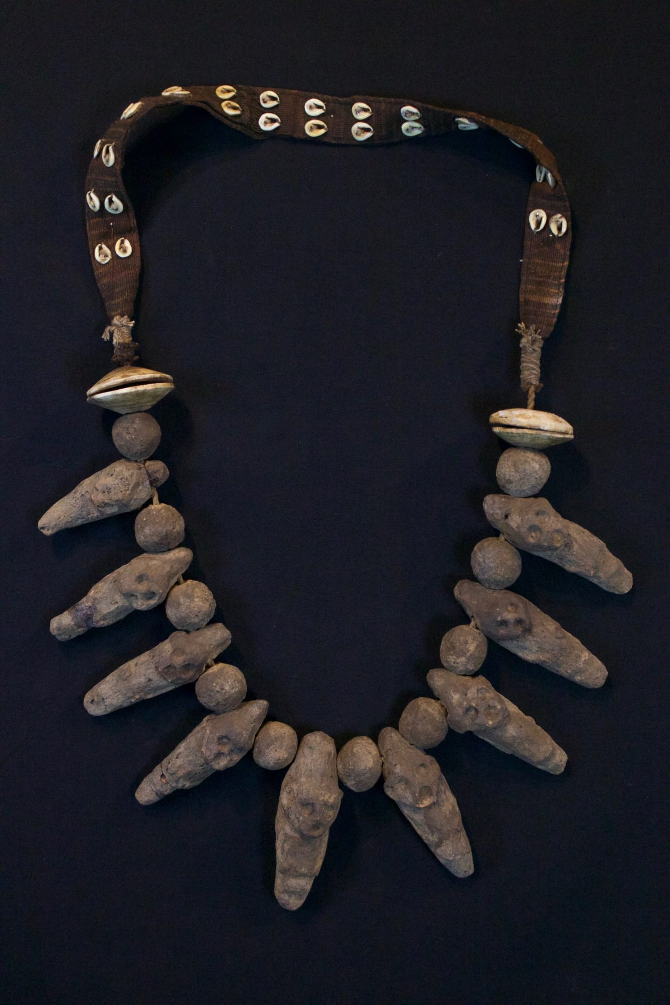 "Shaman Amulet Necklace, Timor Island, Lesser Sunda Islands, Indonesia, Early 20th c, Ceramic stone figures and beads, shell, cotton. Worn by the shaman for healing ceremonies. 20 ½"" x 11"" x 1 ¾"", $650."
