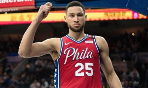 Ben Simmons in a red Philadelphia 76ers jersey holding his arm up celebrating after scoring, looking right into the camera.