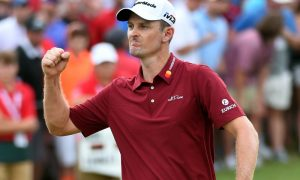 Justin Rose celebrating a made putt at the PGA Tour, wearing a red polo, white hat, and fist pumping in the air.