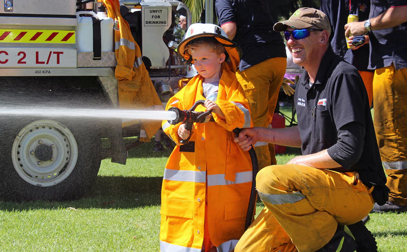 Alex Mullins, 3, of Coolup tries the hose aided by Roelands/Olive Hills Bushfire Brigade volunteer Jeremy Gunson (Photo: Harvey-Waroona Reporter)
