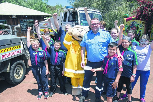 Bedfordale Bush Fire Brigade member Gary Vince collects the donation from Armadale Scouts member Blake Webster (front). Photograph – Aaron Van Rongen