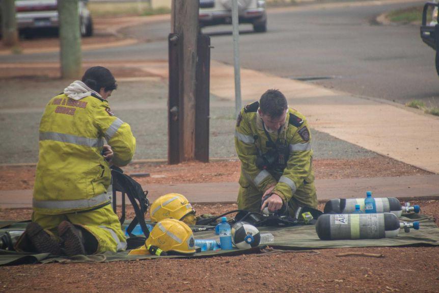 Firefighters change over oxygen tanks at a house fire in Kalgoorlie-Boulder.(ABC Goldfields-Esperance: Jarrod Lucas)