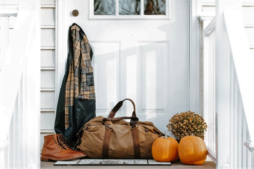 Pumpkins, duffel bag and coat hanging on farmhouse door