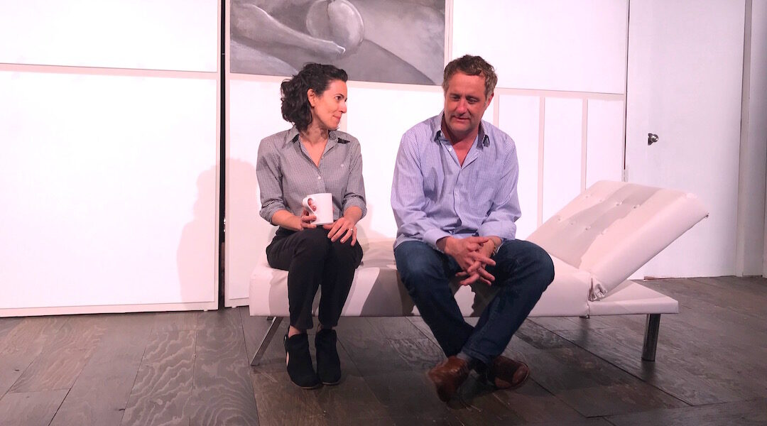 Two actors sitting on stage