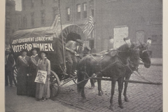 """Three women stand at a covered wagon with the words """"Just Government League, Votes for Women"""""""
