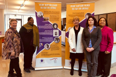 Five women stand in front of a exhibit devoted to Maryland suffragists