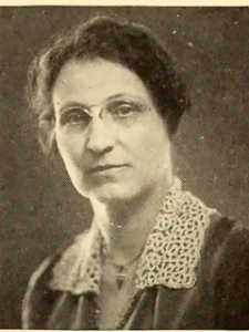 Annie Heloise Abel with hair in a bun and with wire glasses, wearing a dress with white crochet collar