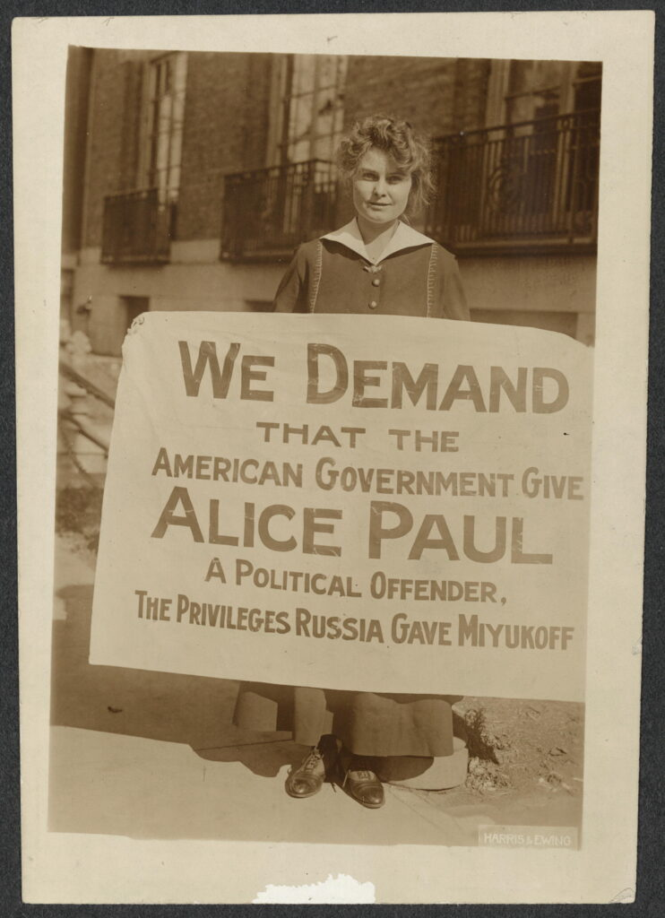 Informal portrait, full-length, Lucy Branham, facing forward, standing in front of a building and holding a sign,