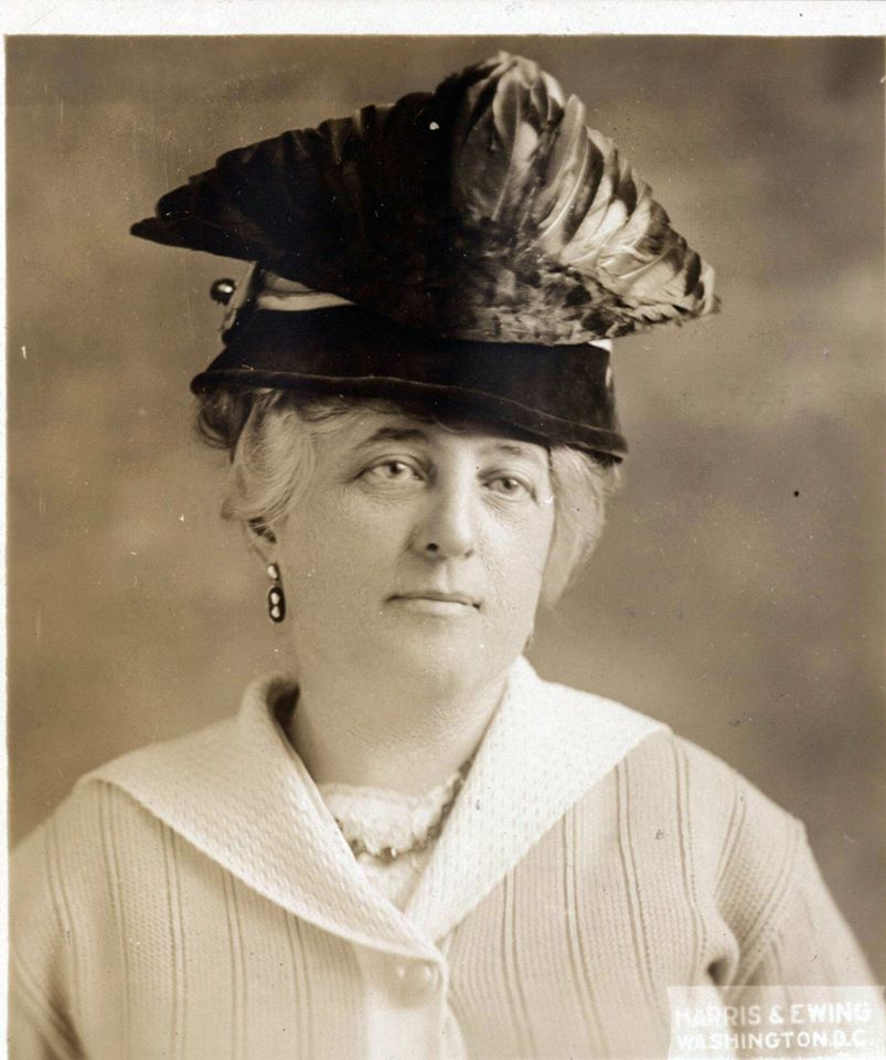 Minnie Brook portrait. She is wearing a large triangular hat.