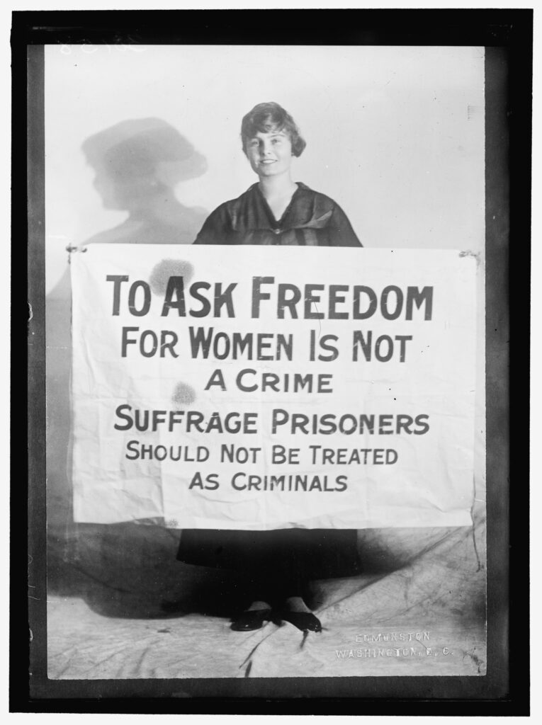 Lucy Branham holding a poster that says