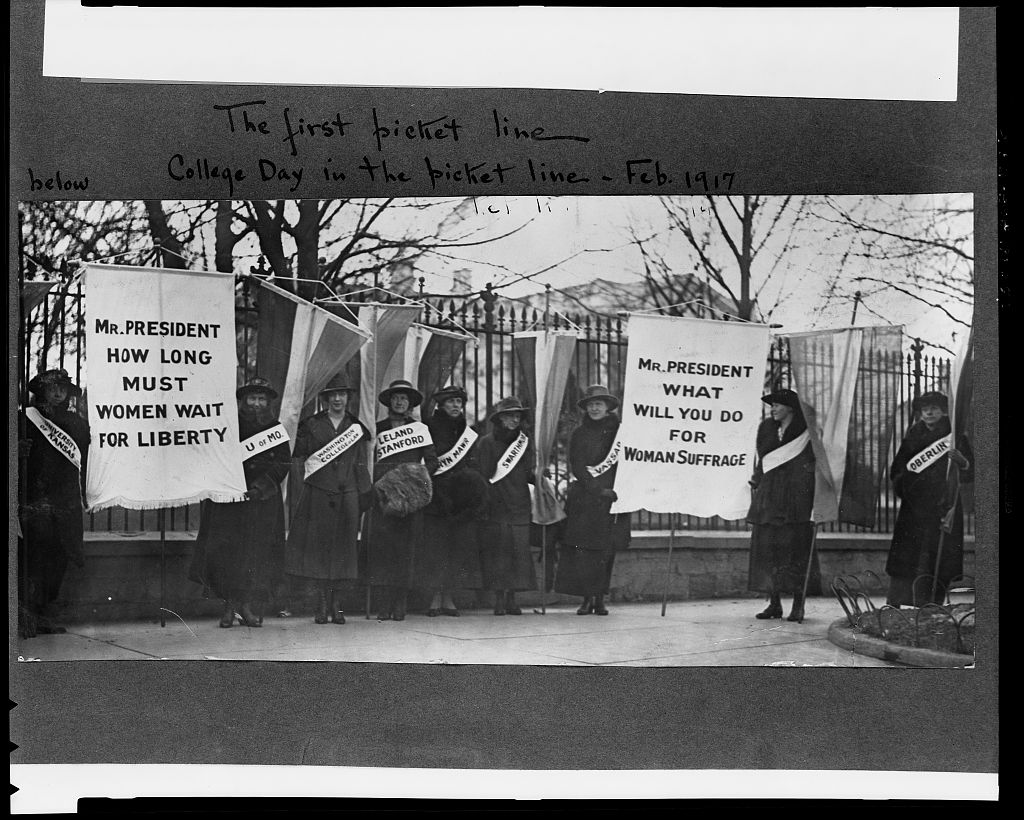 Suffragists carrying banners in front of White House, including the banner that says