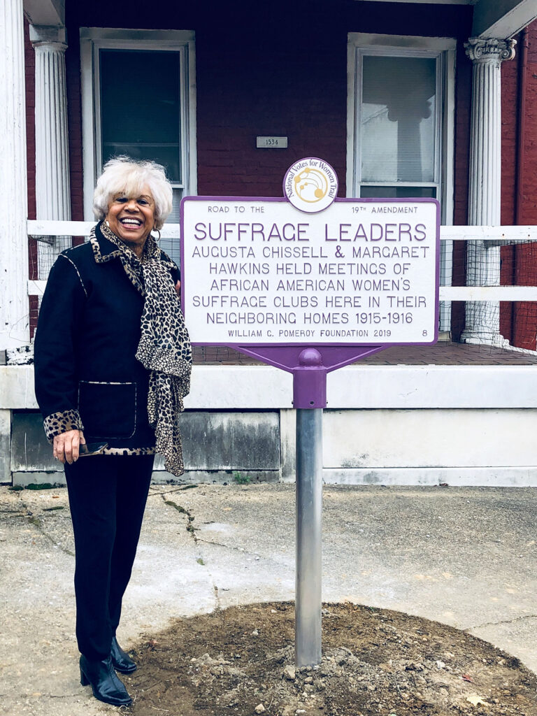 Carolyn Chissell stands next to a historic marker celebrating Augusta Chissell and Margaret Hawkins.
