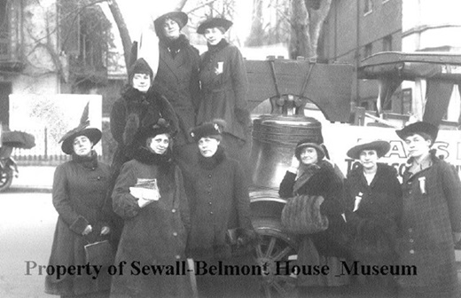 nine women dressed in black coats and hats in front of the Women's Liberty Bell possibly on a float