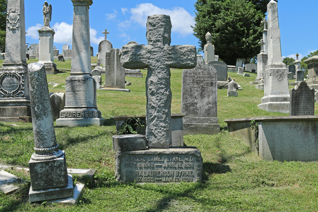 Gravestone of Laura L. Byrne. It is a large stone cross set on a rectangular base.
